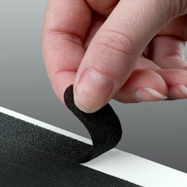 hand peeling back black adhesive tread