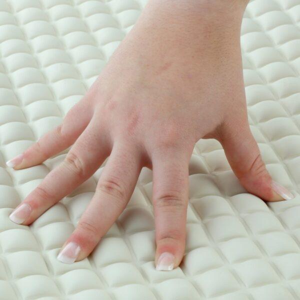 Cream Pillow Top Bath Mat with Hand Pushing Down